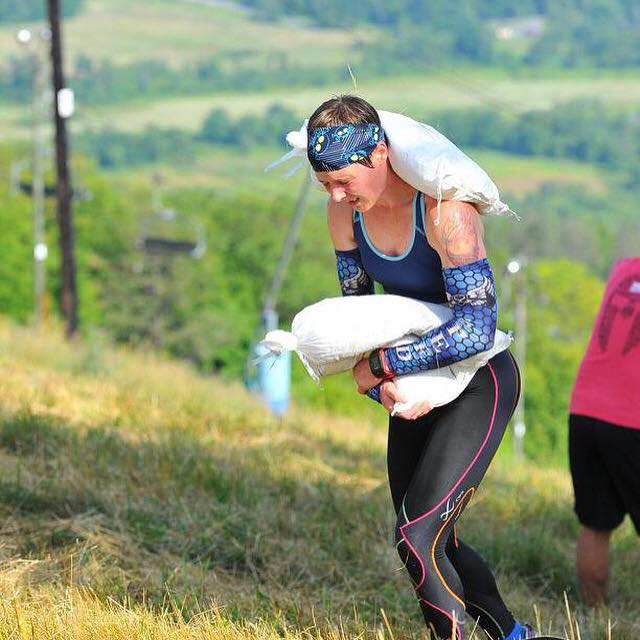 Strength & Speed Athlete Sam Oleskey carrying the double sandbag up a Spartan mountain.
